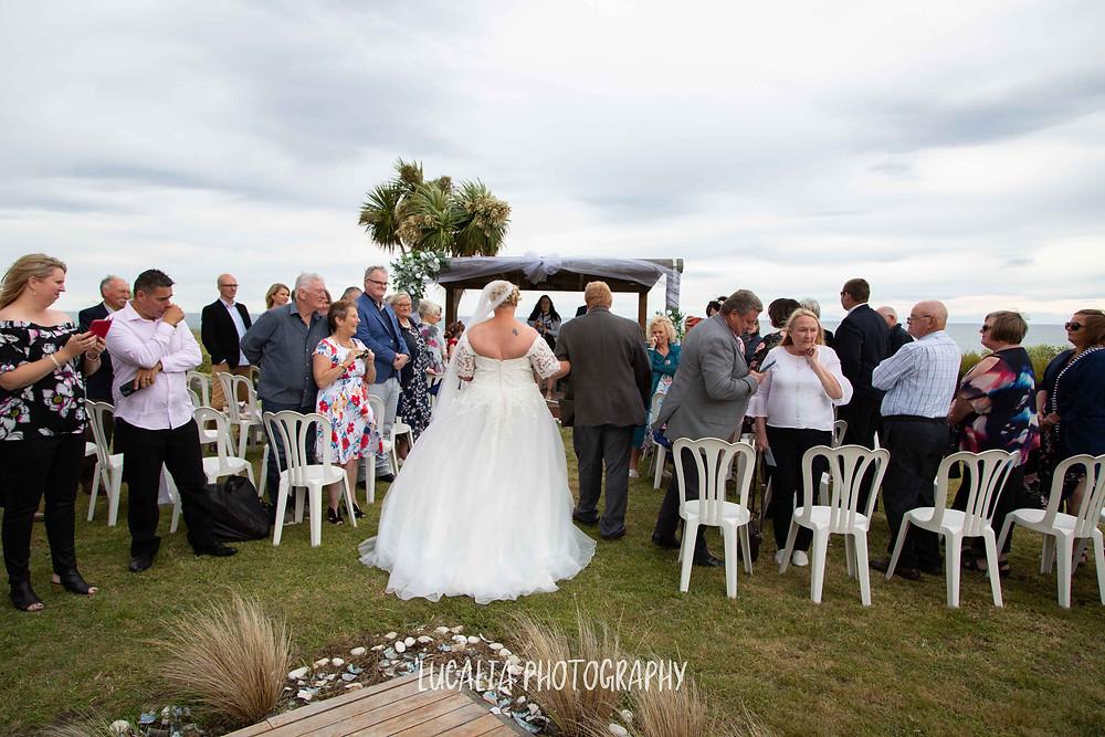 bride walking down the aisle at her wedding ceremony, Waimeha Camping Village, Ngawi, Wairarapa wedding