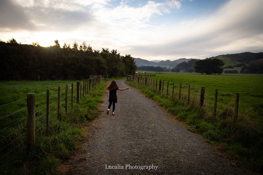 girl runs down a lane through fields with mountains in the background, Wairarapa family photographer
