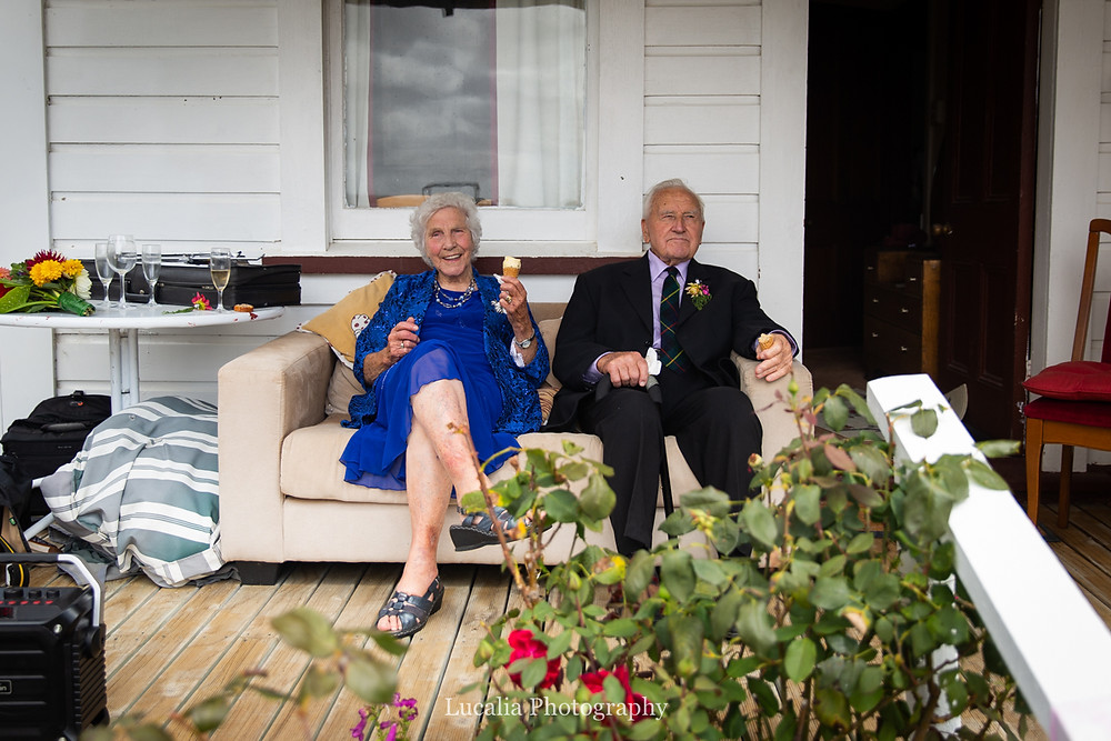 grandparents eating icecream at wedding reception sitting on verandah couch, Wairarapa wedding photographers