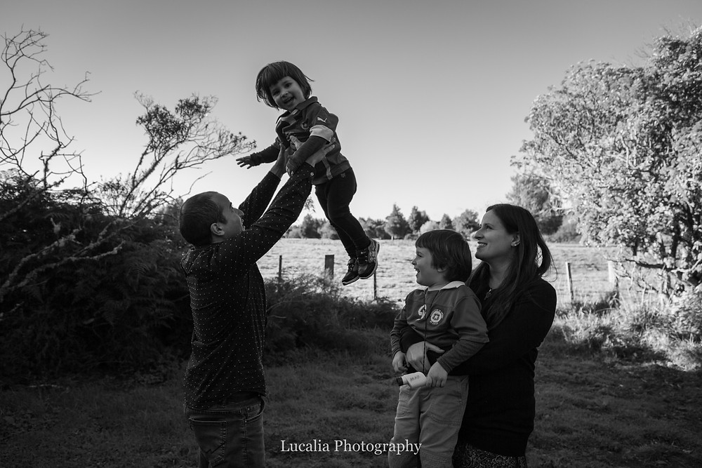 dad throwing son into the air with mum holding other son smiling, Wairarapa family photographer what to wear