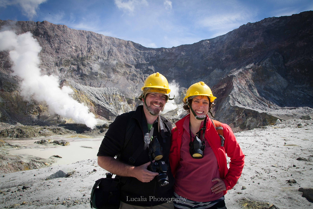 Newly married couple wearing helmets and gas masks White Island Tour active volcano on their New Zealand honeymoon