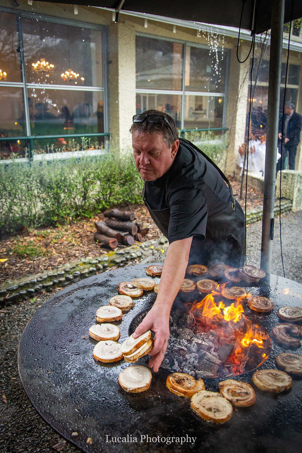 head chef Dale Keith cooking pork outside over wood at Rose & Smith at Tauherenikau Wairarapa wedding venue