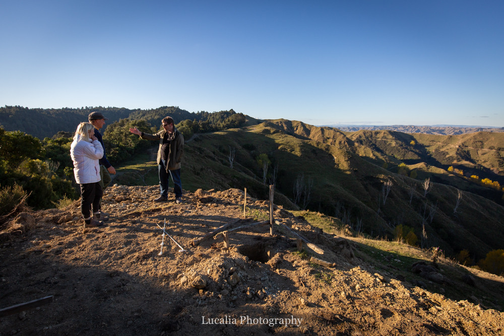 three people discussing hut plans on top of a hill at High Peaks Farm Stay, Mangamahu, Manawatu-Wanganui, New Zealand