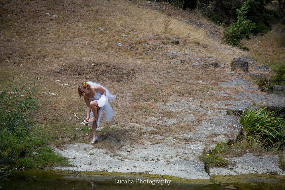 bride takes shoes off to walk across river, Wairarapa wedding photographers