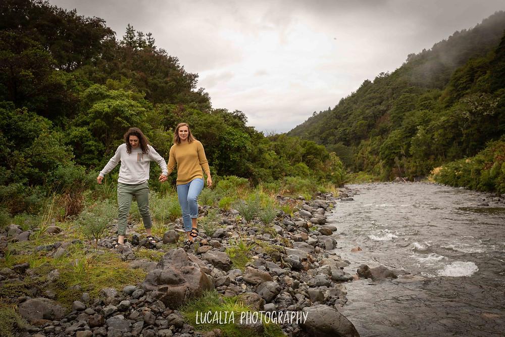 couple walking on river rocks holding hands, Mt Holdsworth Wairarapa
