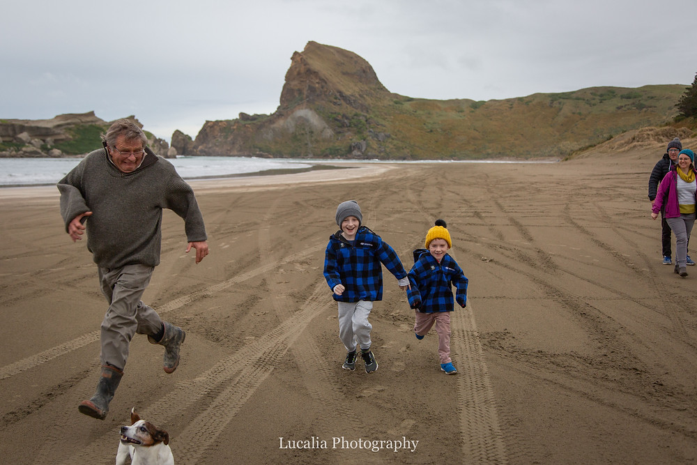 two boys running along the beach with grandad and dog, Castlepoint Wairarapa family photographer