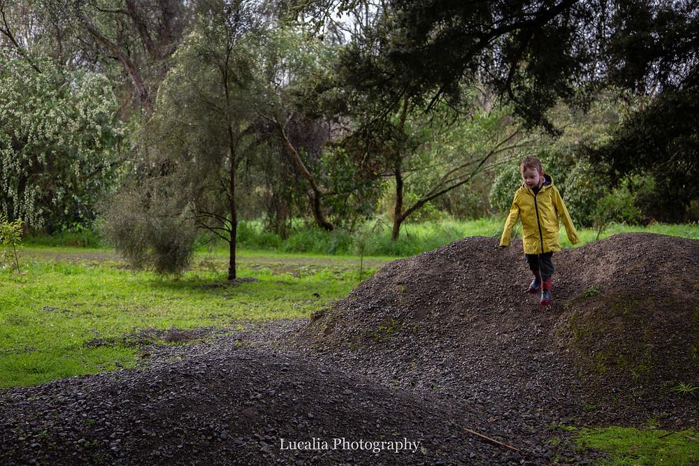 boy in yellow rain coat running down pile of gravel with trees, Wairarapa family photographer