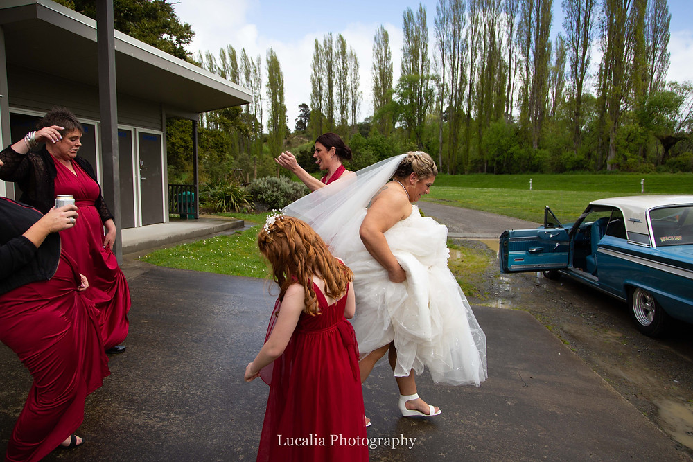 bride and bridesmaide walking towards classic car in a forest, Wairarapa wedding photographer