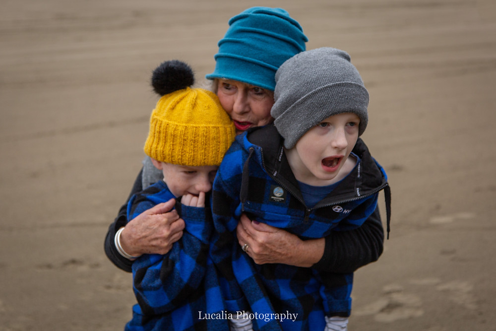 grandma hugging two grandsons on the beach, Castlepoint Wairarapa family photographer