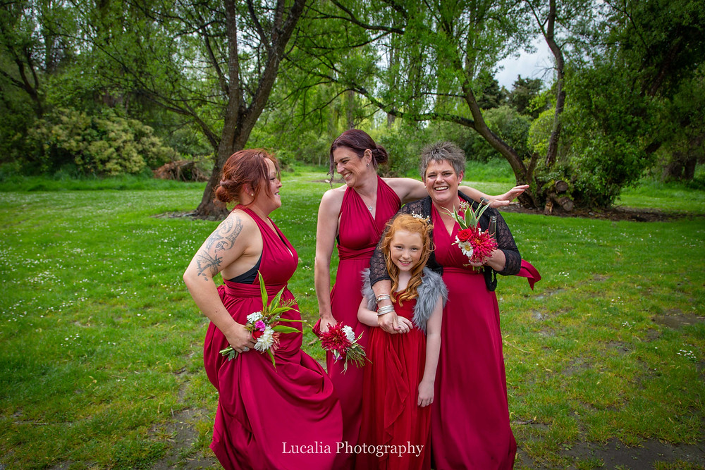 bridesmaids in red dresses laughing with trees in the background, Wairarapa wedding photographer