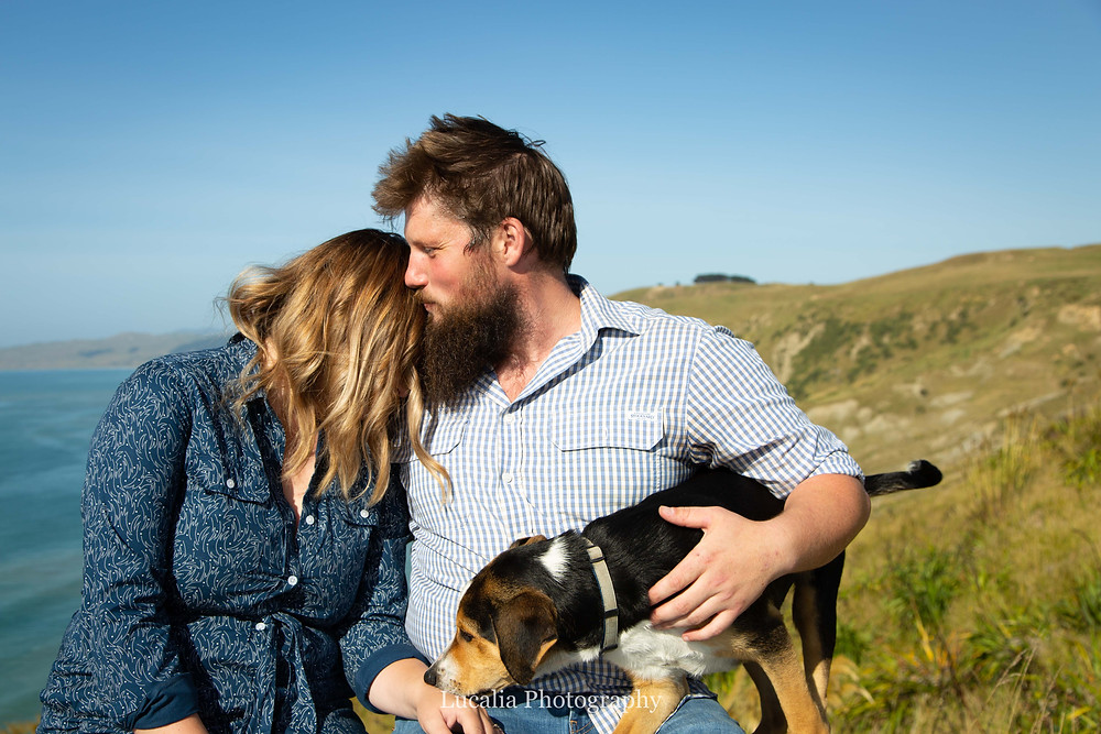 engaged couple with their dog sitting on top of a hill, Castlepoint Wairarapa