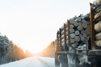 Truck with timber logs on a winter road.