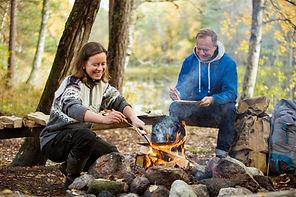 Man and woman making pancakes on campfir