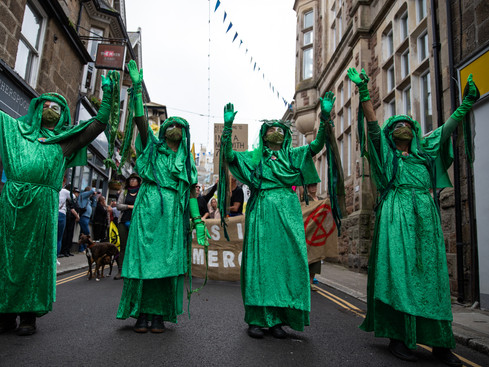 """Extinction Rebellion (XR) activists take part in the """"Sound The Alarm"""" march during the G7 summit in Cornwall on June 11, 2021 in St Ives"""