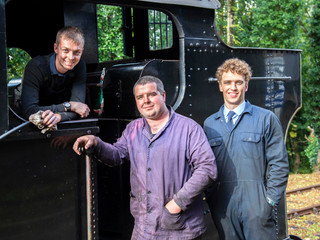 The Driver, Fireman and Trainee Fireman stand next to their steam train at the Bodmin and Wenford Steam Railway.
