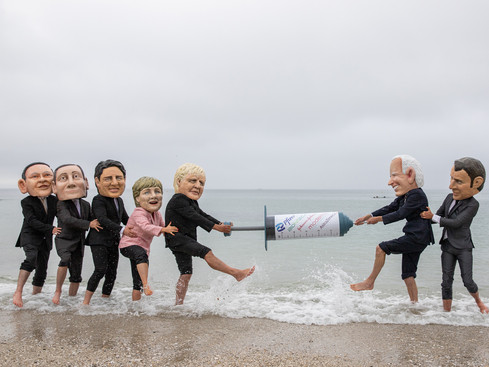 FALMOUTH, ENGLAND - JUNE 11: People's Vaccine Alliance campaigners pose as G7 leaders fighting over a COVID- 19