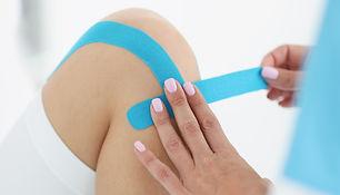 doctor-glues-kinesio-tape-patients-knee_2.jpg