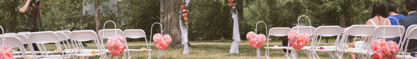 Mickey head kissing balls pomanders line this wedding aisle to match the Disney theme with a wonderful floral garland arch for the couple to marry under