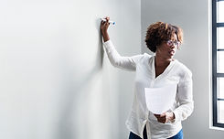 Black woman writing on a whiteboard.jpg