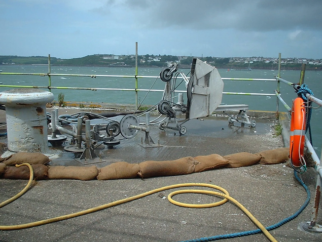 A diamond wire saw on a concrete base near the sea
