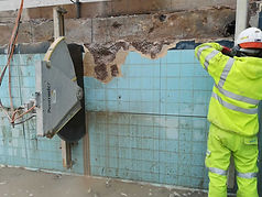 A large circular saw cutting vertically into a blue tiled wall.jfif