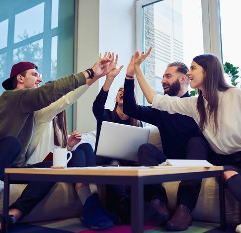 En arbetsgrupp sitter runt ett bord och gör en hive five och skrattar ihop