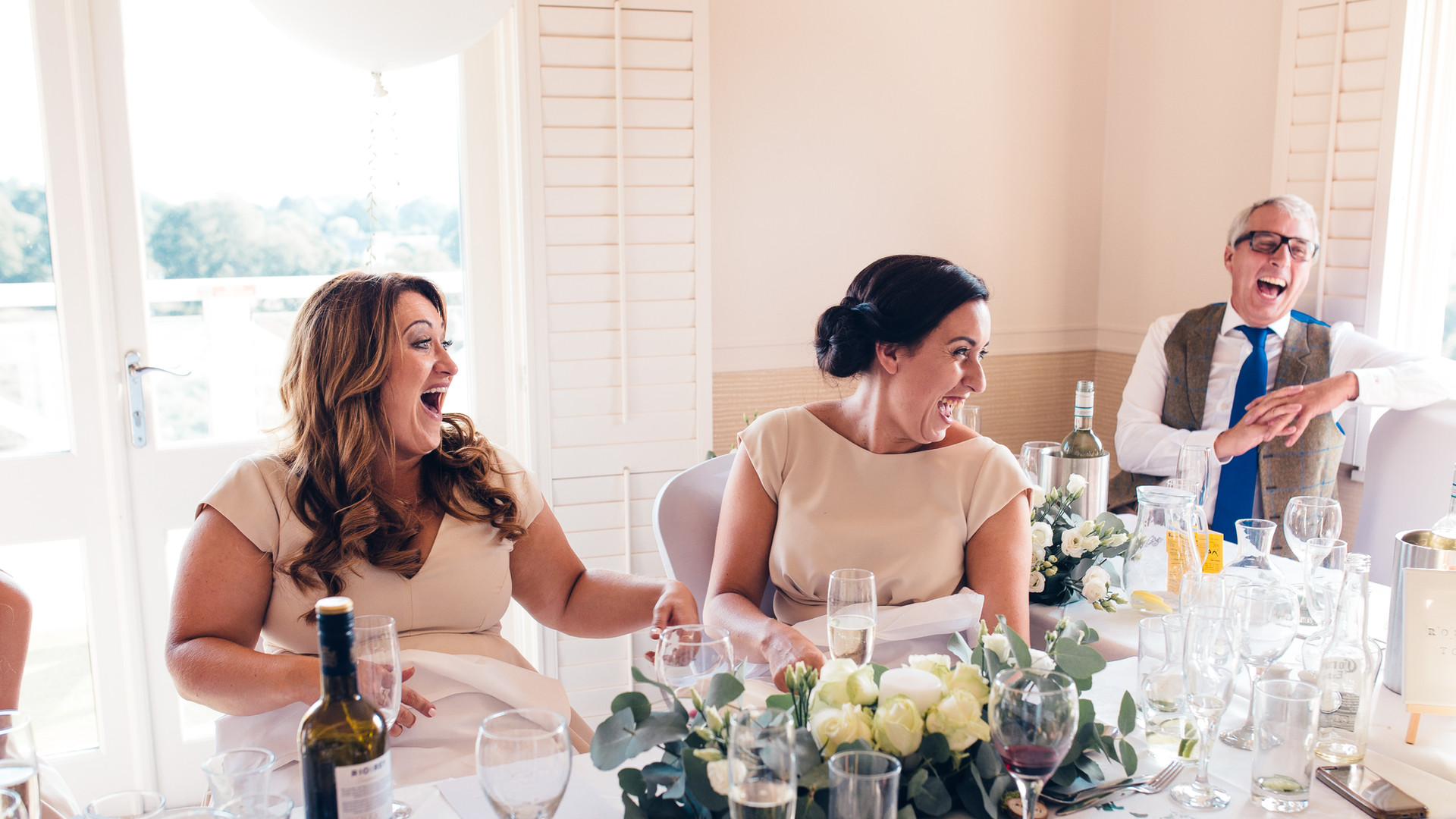 Wedding guests laughing during speeches at Reigate Heath Golf Club, Surrey