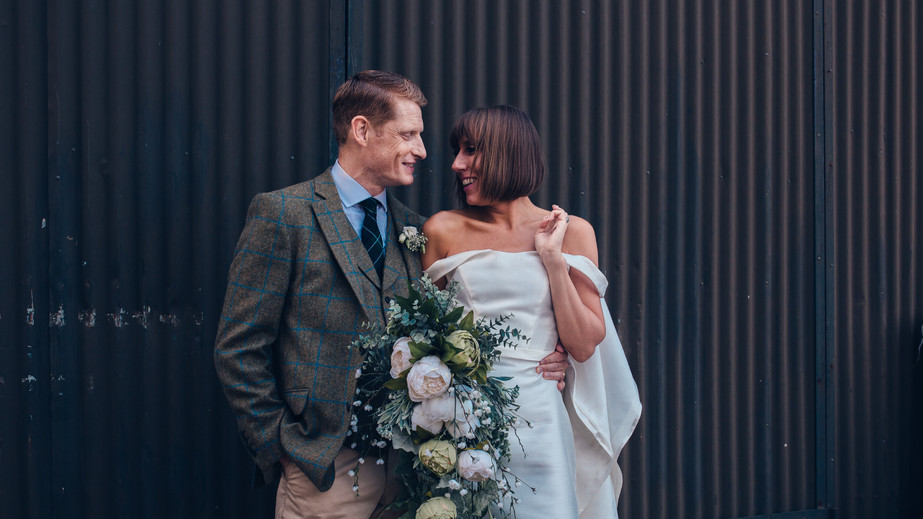 Couple wedding portrait in front of industrial farm building