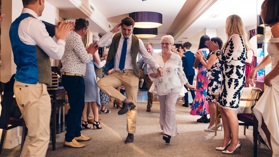 Wedding guests line dancing to Ceilidh band during summer wedding in Surrey