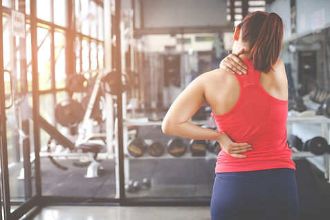 Women with back pain in gym.jpeg