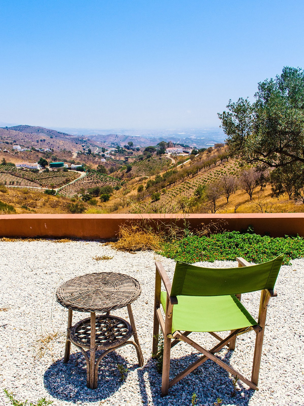 Wicker table and folding chair with view of mediterranean countryside