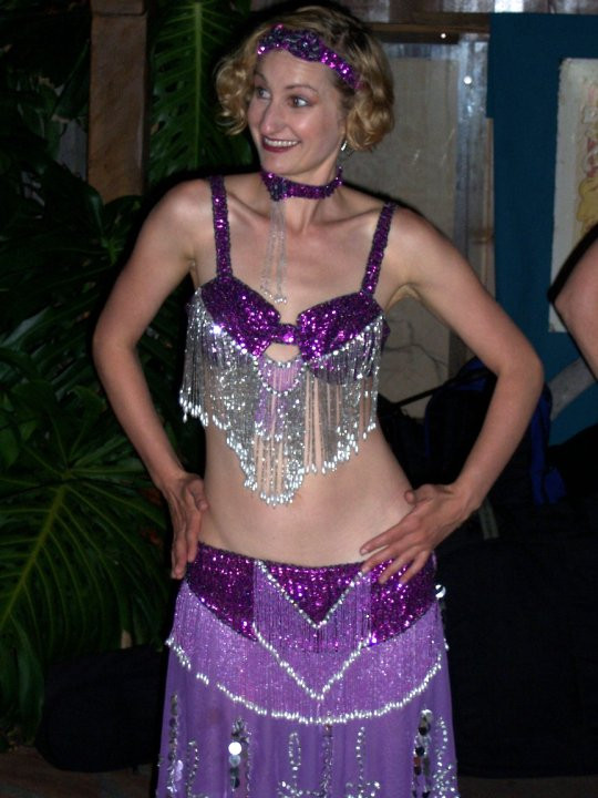 Blonde woman in a purple sequined belly dance costume