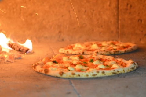 Pizzas cooking in the wood fired oven
