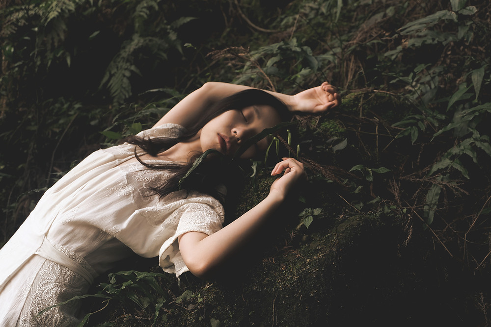 Woman sleeping in forest