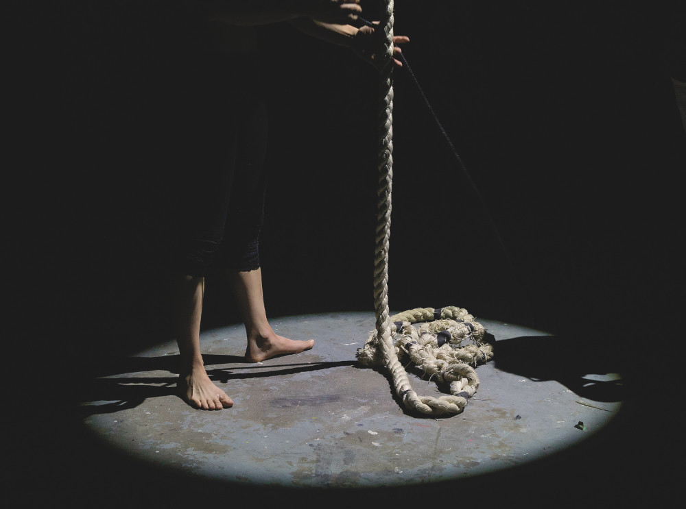 Person in the Dark Holding a Rope