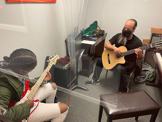 Mr Chris teaching the bass guitar