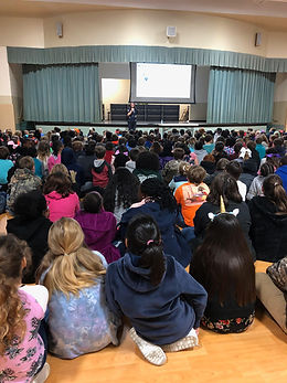 Elementary students at assembly with children's book author Gillian McDunn