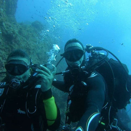Divers exploring a wall, Diving in Sicily