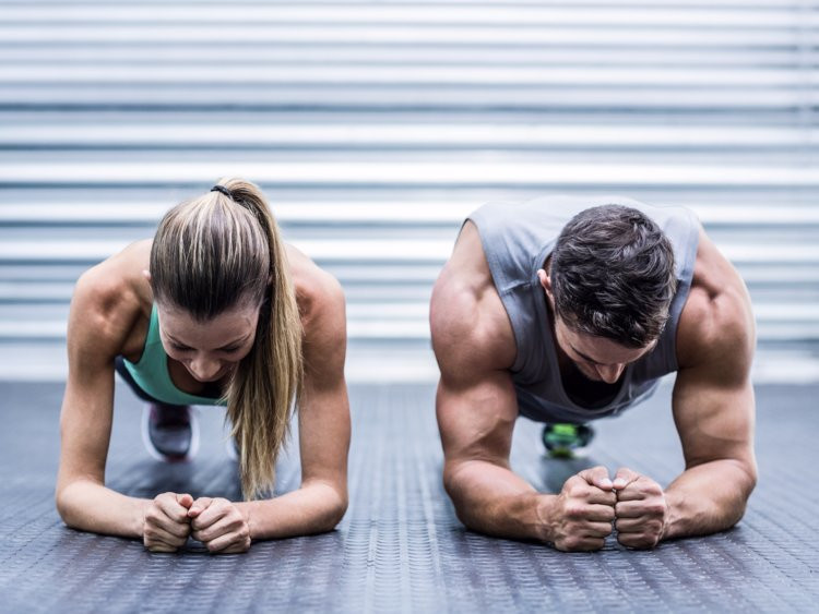 Couple doing abdominal plank exercise for fitness testing
