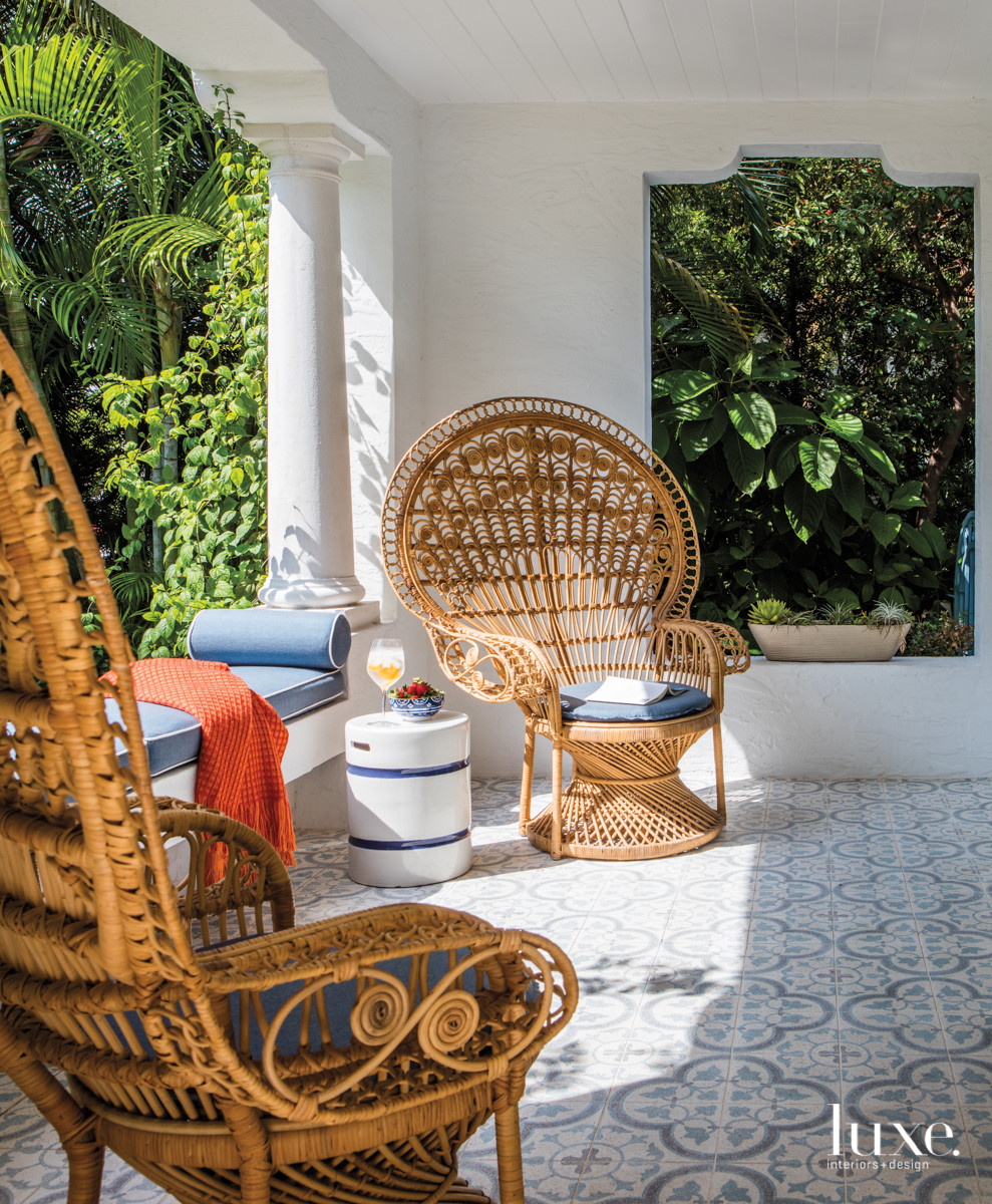 Architect and general contractor Carlos Figueroa created a covered loggia furnished with wicker peacock chairs and a Serena & Lily garden stool on concrete-cement flooring. The cushions on the chairs and the built-in bench--designed to offer more seating without blocking the garden view--are from Wall Boutique.