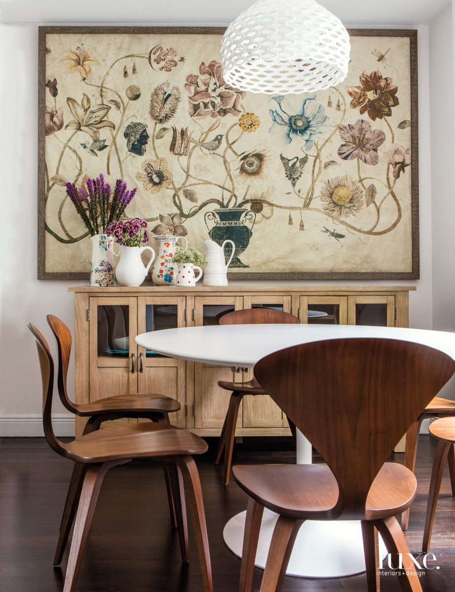 In the breakfast room, Saliba framed a paper mural to display over a Pottery Barn cabinet. A Patricia Urquiola pendant from The Lighting Studio hangs above an oval Saarinen table surrounded by Cherner side chairs from Design Within Reach.