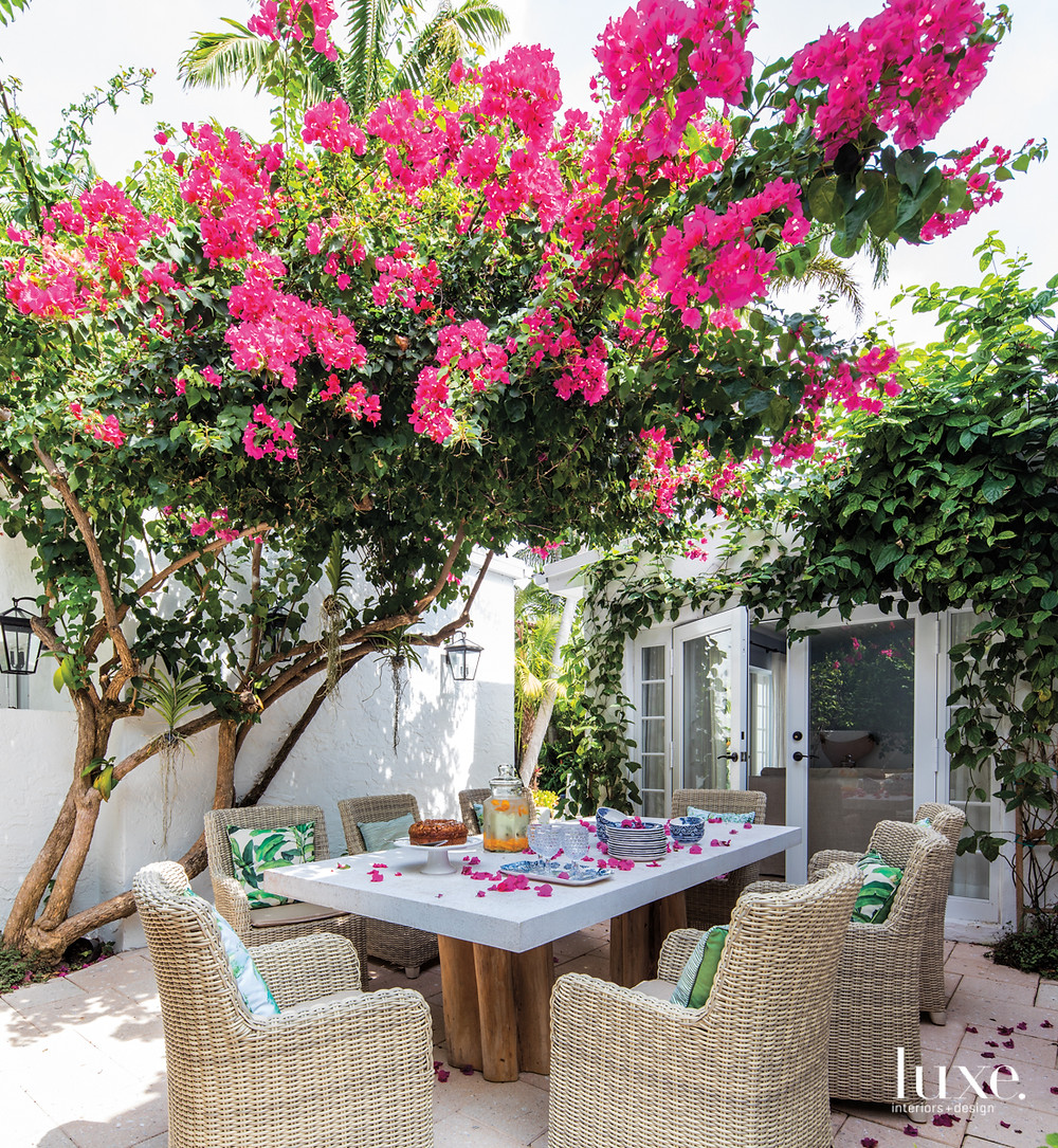 A thriving bougainvillea tree injects a vibrant fuchsia shade in the patio, where a Janus et Cie table and chairs rest on pavers by Madison Construction Group. La Casona Garden designed and installed the landscape.