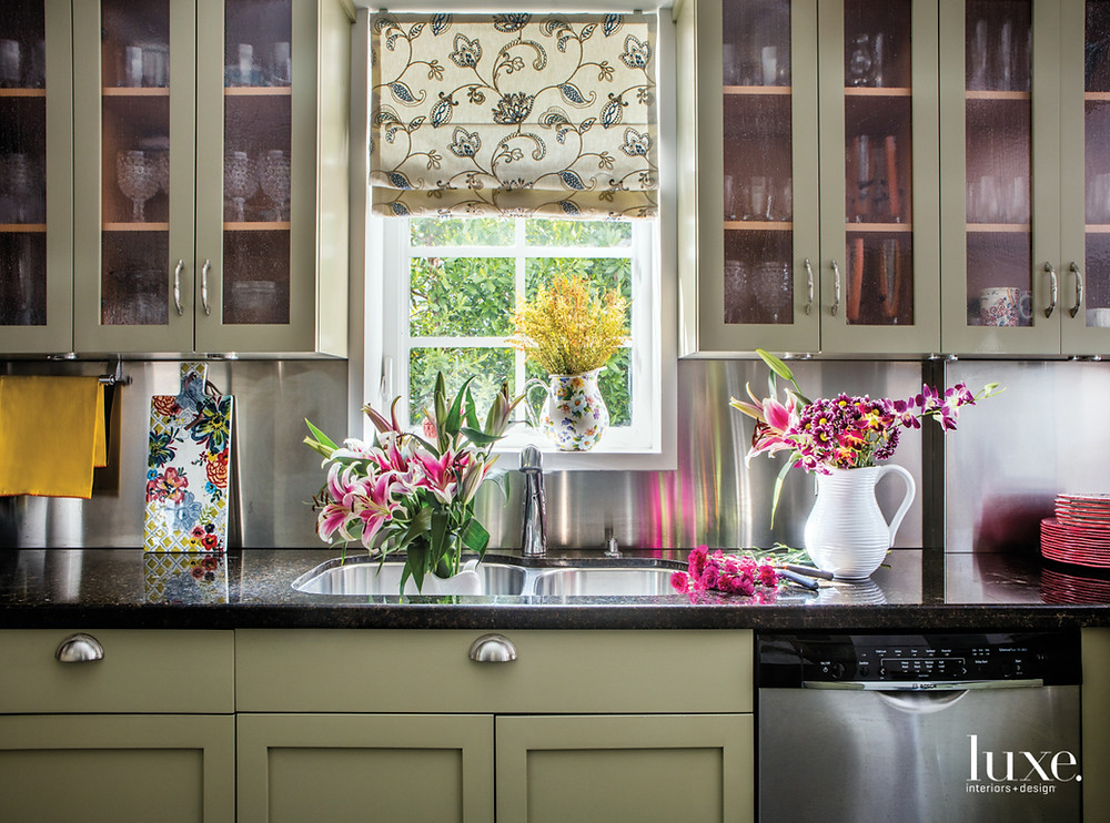 """The Ubatuba Countertops and the cabinets were kept because the owner was afraid a new kitchen would look too modern,"""" Saliba explains, adding that the cabinets were originally a cherry hue. The window valance was made with an embroidered fabric from Wall Boutique."""