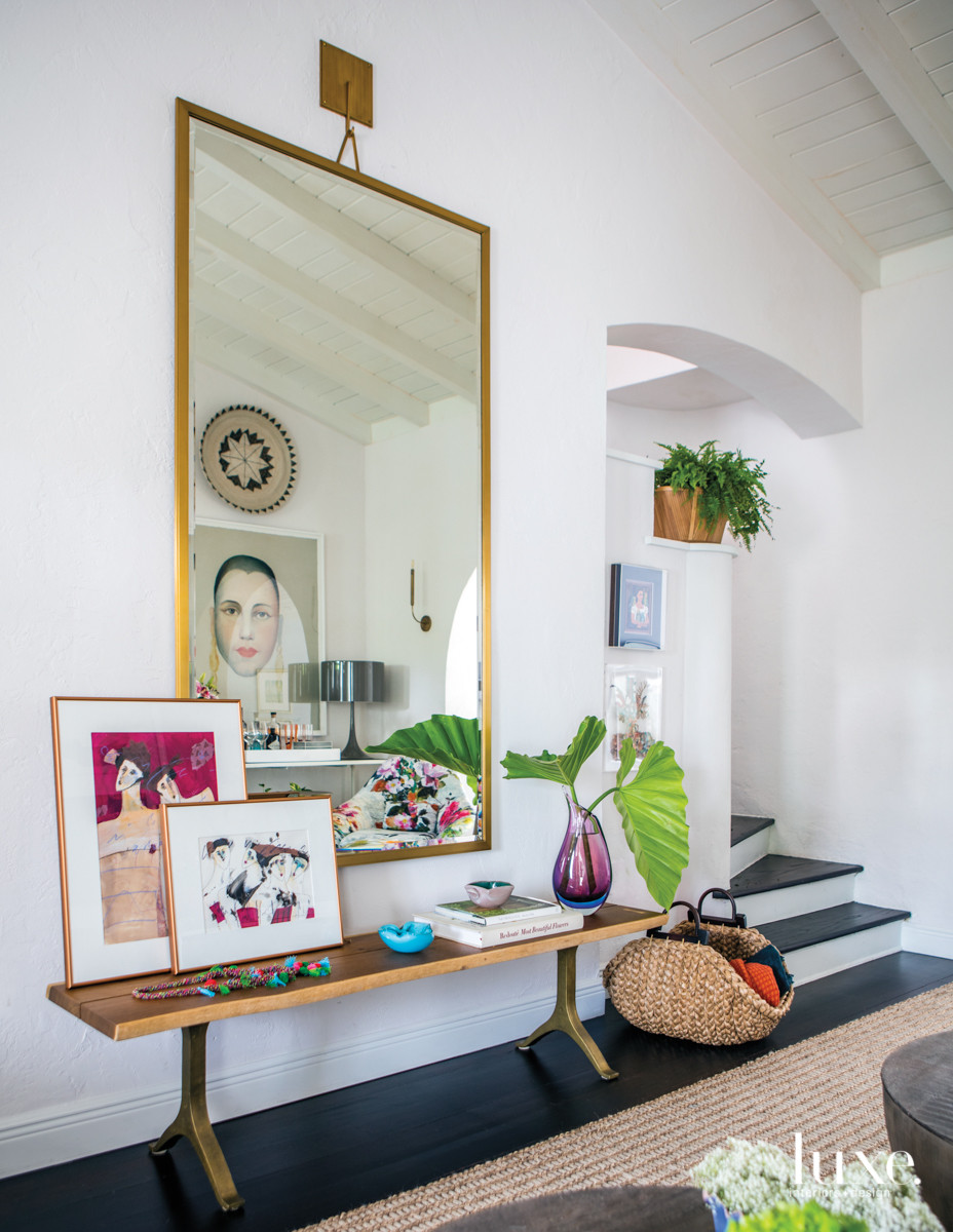 Underneath an RH mirror in the living room, a live-edge wood bench from Anthropologie offers a display for accessories, including artwork from the client's collection. The original red wood floors received a darker stain, and the walls were painted Sherwin-Williams' Ibis White.