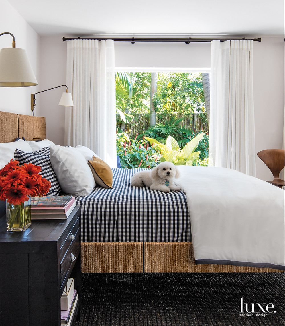 A cozy bedroom in the property's cabana hosts a Serena & Lily bed and lamps. Near the Cherner side chair from Design Within Reach, draperies by Wall Boutique frame views of the lush backyard. The linens, nightstand and rug are RH.