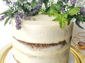 Nearly naked single wedding tier with a wild crescent of flowers