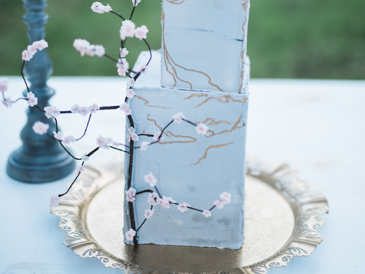 Concrete cake with gold kintsugi detailing and a climbing cherry tree accent