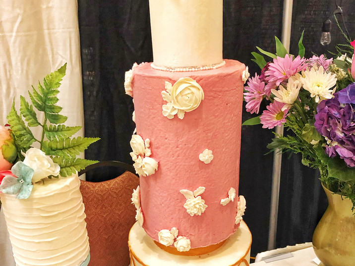 Gold geometric designs, tall tiers, modern silhouette, and handpiped flowers