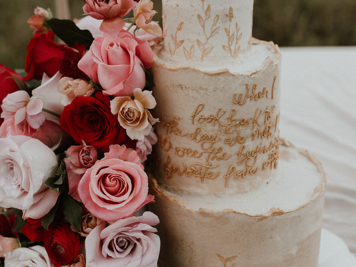 Romantic handpainted cake with calligraphy quote and a wild cascade of roses