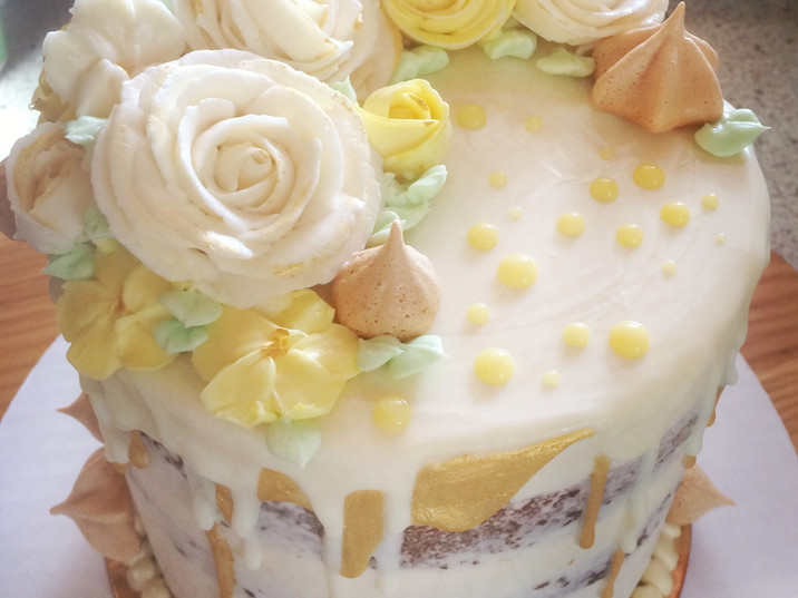 Single tier statement cake with hand piped roses, meringues, and gold